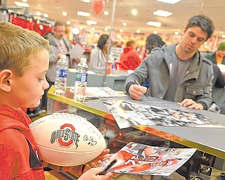 """Peyton Weaver of Middlefield walks away with a poster, photograph and football autographed by Ohio State University wide receiver Dane Sanzenbacher, in background. Although only 9, Peyton claims to have been fan of OSU """"forever."""""""