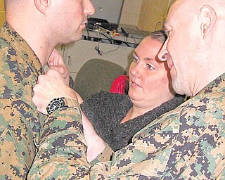 At right, Marine Lt. Col. William J. Truax, officer-in-charge of coordination, liaison and assessment team Latin America, Fort Story, Va., and Amanda Rudolph, put on Gunnery Sgt. Robert A. Rudolph, of Youngstown, the pin to his current rank. Amanda is Rudolph's wife.