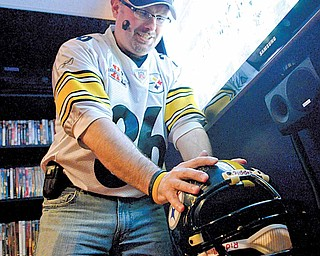 Jim Davis rubs a Steelers helmet in his Austintown basement for good luck. The helmet is signed by four members of the Steel Curtain Steelers teams. The Steelers scored their first touchdown of the night minutes later but eventually lost the game.