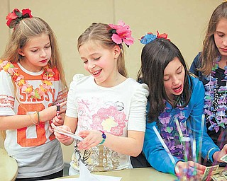 Abigail Sudano, 11, of Berlin Center (second from left) opens a card from a friend at her birthday party at the Salem Community Center Saturday evening. She gets some help from friends Katie Henderson, 10, of Berlin Center, Sudano, Angela Fusillo, 10, of North Jackson and Kendall Dye, 11, of Berlin Center. Sudano asked for donations instead of birthday gifts so she can help local causes.