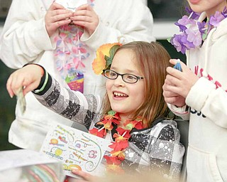 Sara Sudano, 10, of Berlin Center, opens a card from a friend at her birthday party at the Salem Community Center Saturday evening. Sara, along with sister Abigail, 11, asked for donations instead of birthday gifts so they can help local causes.