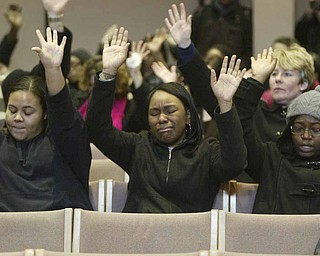 Jeanna Denson, left, Dana Thomas and Dessera McClendon participate in Monday's prayer service at Youngstown State University, after weekend shootings left one YSU student dead.
