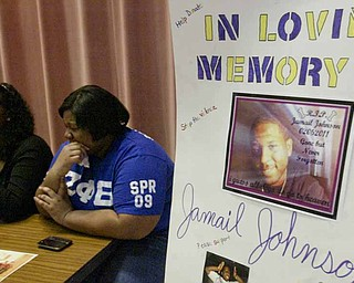 Anjalia Lyons, left, and Charesse Alexander, Youngstown State University students and members of sorority Zeta Phi Beta, collect donations before a campus prayer service for shooting victim Jamail Johnson's family.