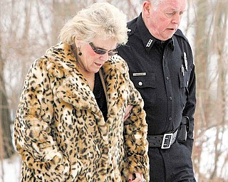 Dr. Cynthia Anderson, president of Youngstown State University, walked with a YSU police officer near the scene of a shooting at an off-campus fraternity house Sunday. Six students were hit by the gunfire, one of them fatally.