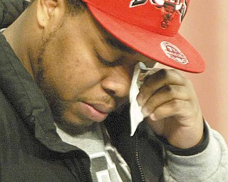 YSU student Adrian Watson wipes away a tear before reading a poem during a prayer service on campus Monday. Watson was friends with Jamail Johnson, the man killed in the weekend shooting at an off-campus party. He wrote the poem for his late friend.