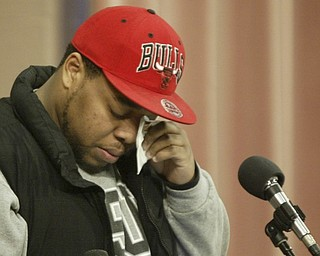 William D. Lewis the vindicator YSU student Adrian Watson wipes away atear before reading a poem during a prayer service on YSU campus Monday. Watson knew shooting victim Jamil Johnson and wrote poem about him.
