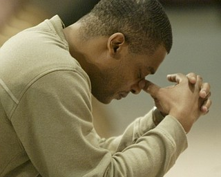 William D. Lewis the vindicator YSU student Darian Rich during a prayer service on campus Monday.