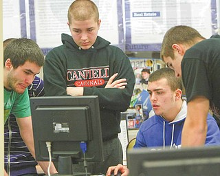 Canfield High School students work to edit a commercial they made, advertising the clothing they will sell through their Intro to Business class. Seniors Brad Kelly, left, Ryan Camardo and Ryan O'Hara and freshman Alex Heldrerk shot the video in class last week.