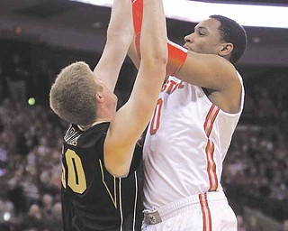 Ohio State's Jared Sullinger, right, shoots over Purdue's Travis Carroll during the first half of an NCAA college basketball game Tuesday, Jan. 25, 2011, in Columbus, Ohio.
