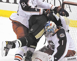 Pittsburgh Penguins' Jordan Staal, center, is shoved into Columbus Blue Jackets goalie Steve Mason (1) by defenseman Fedor Tyutin (51) during the first period of an NHL hockey game in Pittsburgh, Tuesday, Feb. 8, 2011.