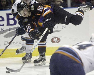 Ryan Belonger makes a one legged shot past Jordan Young of Indiana Wed morning at the Covelli Center. The Phantoms took on the Indiana Ice in a 10 am game with school children from the area attending.