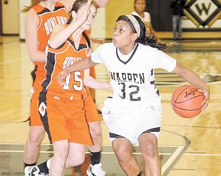 Warren Harding's Kourtney Williams (32) drives to the hoop as (15) Paige Loychik (15) and Taylor Williams defend during their basketball game Thursday in Warren. The Tigers (17-1) took the lead midwaythrough the first period and never trailed on the way to a 45-44 victory.