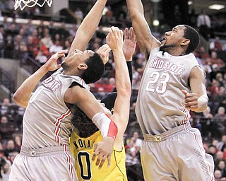 Ohio State's Jared Sullinger, left, and David Lighty go up for a rebound over Michigan's Zack Novak during the second half of an NCAA college basketball game in Columbus, Ohio, Thursday, Feb. 3, 2011. Ohio State won 62-53. (AP Photo/Paul Vernon)