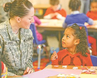 Jessica Myers from Youngstown State University's Armed Forces Student Association and Gianna Zamudio, a kindergarten student at Zion Christian School at Zion Lutheran Church in Youngstown, share a quiet moment while creating Valentine's Day cards to be sent to troops in Afghanistan. George McDonnell, a local business leader, has been instrumental in providing connections for delivery of the valentines. The event was sponsored by Shepherd of the Valley Home Health.