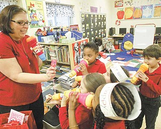 Teacher Andrea McGoogan and a group of her first-graders talk into toy microphones during a Valentine's Day party in their room Monday. The microphones were a present to each child from McGoogan.