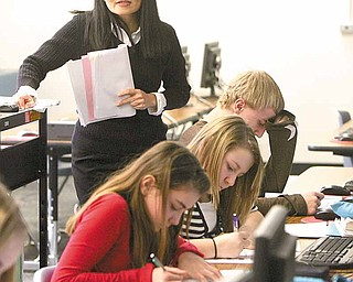 Siao looks on as students in her seventh-grade class practice writing characters in Chinese. From front to back are Canfield Village Middle School students Nikki Tuchek, Paige Modareli and Nick Sammarco.