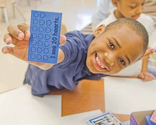 Darnell Jones, 6, a kindergarten student at Taft Elementary School on Youngstown's South Side, shows off a stamp he uses to learn counting and reading. Through DonorsChoose.org, teachers at the school have received educational resources and teaching aids through donations — sometimes from complete strangers.