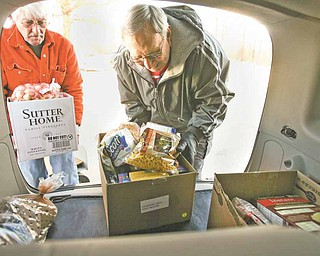 Bob Rose, left, and Gerald Rassega, load boxes of food from the Vienna Ecumenical Food Pantry on Warren-Sharon Road into the back of a car. The pantry is operated by three churches — Vienna United Methodist, Vienna Presbyterian, and St. Thomas the Apostle Catholic Church, formerly St. Vincent de Paul Church.