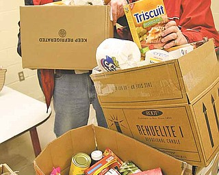 Joe and Ruth Hayes, who helped found the food pantry in 1985, pack food boxes for distribution. The pantry is located in St. Thomas the Apostle Catholic Church on Warren-Sharon Road in Vienna.