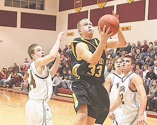 Tom Oliver (33) drives past Mike Thorpe (22) and Isaac Schuster (44) of South Range during their game Wednesday night.