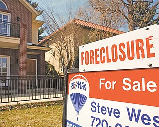In this April 4, 2010 file photo, a forclosure sign tops the for sale sign outside a home in Denver.  Foreclosure activity jumped in 149 of the 206 largest metropolitan areas in the U.S. last year, foreclosure listing firm RealtyTrac Inc. said Thursday Jan. 27, 2011.
