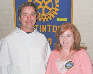 Doing right against blight: The Rev. Greg Maturi, from St. Dominic Church, informed members of the Rotary Club of Austintown about Operation Redemption on the South Side. The area around the church has seen 20 vacant homes demolished, and the 45 that remain are targeted for rehabilitation. Rotary President Susan Leetch, above, right, presented Father Maturi with a certificate of appreciation and showed a book to be donated to Woodside School Library in Austintown, as is done each week in honor of the speaker. At the same meeting, Jennifer Connolly was inducted into the Rotary Club. She is the administrator of Briarfield Assisted Living in Austintown.