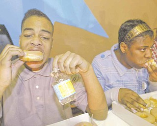 Monty Robinson, 17, of Youngstown, left, was the winner of a doughnut-eating contest at the fourth annual Criminal Justice Fair on Saturday at Heart Reach Ministries in the city. He ate five-and-a-half doughnuts in three minutes, beating out several other competitors, including his sister, Monique, at right. This was the second year Monty won the event.