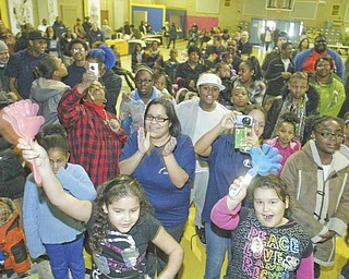 Spectators of all ages cheer on participants in a doughnut-eating contest Saturday as part of the fourth annual Criminal Justice Fair at Heartreach Ministries.