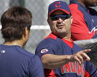 Cleveland Indians manager Manny Acta, right, talks with outfielder Shin-Soo Choo during baseball spring training practice Thursday, Feb. 17, 2011, in Goodyear, Ariz.