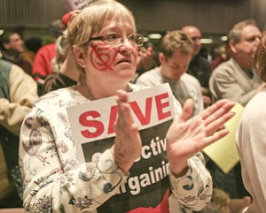 Kate Renfeld of Campbell, a school teacher, painted her face and applauds at a rally against Senate Bill 5 Monday night in YSU's Kilcawley Center.