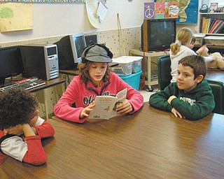 "Sharing their talents: Seventh-graders from the honors literature class recently shared their storytelling talents with first- and third-graders at St. Patrick School in Hubbard. The readers enhanced their stories with hats and props. Gina Madeline reads from ""The Great Mouse Detective."""