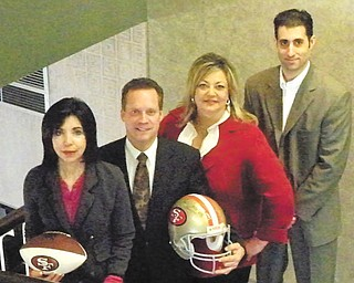 Above, displaying a San Francisco 49ers football and helmet that will be among the auction items at the Mardi Gras are, from left, Denise DeBartolo York, owner of the 49ers; Ted Schmidt, PNC regional president; Liz McGarry, Hospice director of development; and Ryan Pastore, PNC director of client and community relations. Below, culinary art students at Choffin Career and Technical Center were asked to make King Cakes for the party. Cakes, made from two different recipes, were sampled and voted on by McGarry and Terrance Escarco of Hospice and the students. Standing behind Dasia'n Square, who is holding a cake baked from the winning recipe, are, from left, Charles Crosby, Myeila Carter, Tre Little, James Donaldson and Darryl Kempson.