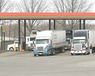 Diesel prices have been increasing. Trucks fill up at the pumps.