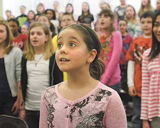 Fifth-grader Alexis Bodnar sings along with classmates during choir practice at Frank Ohl Intermediate School in Austintown. The students will perform the national anthem Friday before the Youngstown Phantoms hockey game at the Covelli Centre in downtown Youngstown.