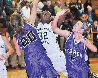 Ursuline's Courtney Powell muscles her way between Lisbon defenders #20 Anna Dunn and #12 Julie Gauntt, while on her way to the basket.