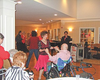 """Time for a dance: """"Let Me Call You Sweetheart"""" was the theme for a Valentine's Day dance at Victoria House Assisted Living Facility, 5295 Ashley Circle, Austintown, where the grand lobby was transformed into """"Club Victoria."""" After residents were treated to a surf-and-turf dinner, music was provided by Steve Fazzini as special guests and a group of ballroom dancers entertained and danced with the residents. Joining in the festivity, above, was Rosemary Yaworsky, a nurse at Victoria House, whose dance partner is one of the residents, Jack Finn."""