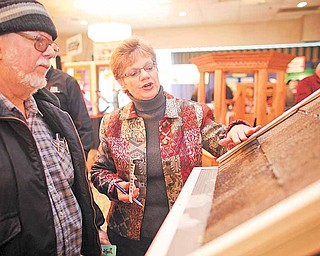 Debbie Martin of Leroy Township explains the Leaf Filter gutter protection system to Dennis Keith of Youngstown at the 60th annual HBA Home and Garden Show at Mr. Anthony's in Boardman Saturday.