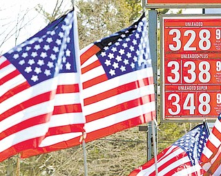 American flags blow in the wind outside a Gibbs gas station where a sign shows the new price of gasoline, Thursday, Feb. 24, 2011, in Topsham, Maine. Gasoline for U.S. motorists already costs more than at any point since 2008, despite ample supplies.