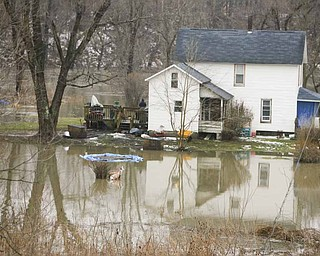 On Front Street in Girard under the viaduct, the Mahoning River creeps up to a house as it overflows its banks.