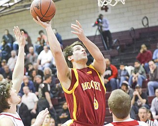Cardinal Mooney's Kevin McGuire (5) scores over Crestwood's Clay Walters (23) during a Division II tournament basketball game Wednesday at Boardman High School. The Cardinals held on to defeat the Red Devils, 61-55.
