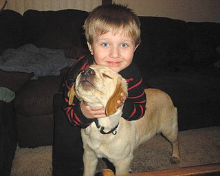 Justin Bish, 3 1/2 years old, is trying to get his new puppy, Sparky, to face the camera so his grandma, Pam Filo of Hubbard, can snap the picture.