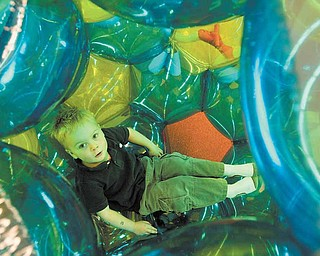 Charlie Sneek, 4, of Boardman, crawls into a bubble and hangs out at Skedaddles Indoor Playground, which opened on Market Street Monday.