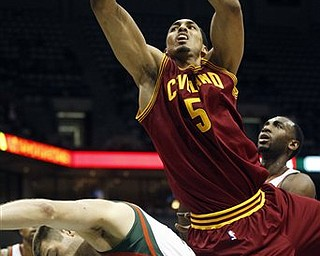 Cleveland Cavaliers' Ryan Hollins (5) is fouled by Milwaukee Bucks' Jon Brockman (40) while going up for a shot during the first half of an NBA basketball game on Wednesday, March 9, 2011, in Milwaukee.