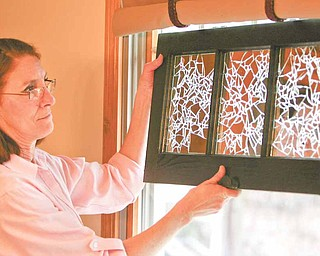 Unusual patterns are highlighted as light from a window flows through a finished window pane that Dru Marchese of Poland decorated with shards of mirror glass. Marchese, diagnosed with multiple sclerosis in 1998, will display her work Saturday as part of an MS Awareness Month art show and auction in Akron.