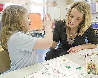 Jodi Kosek, a first-grade teacher at Harding Elementary, high-fives student Savana Cline. Kosek was named Youngstown City Schools' Teacher of the Year in an award ceremony Monday morning.
