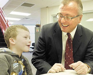 Garry Mrozek, CEO of Hometown Pharmacy Solutions, has a laugh with Struthers Elementary School first-grader Bill Torreance during the start of Hometown Pharmacy's Healthy Kids Free Vitamin Program.