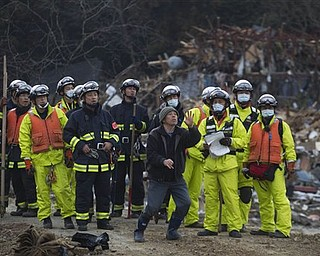 A survivor of the tsunami that swept through his village of Saito, in northeastern Japan, retells the story to a rescue team that arrived to search the area Monday, March 14, 2011. Rescue workers used chain saws and hand picks Monday to dig out bodies in Japan's devastated coastal towns, as Asia's richest nation faced a mounting humanitarian, nuclear and economic crisis in the aftermath of a massive earthquake and tsunami that likely killed thousands.