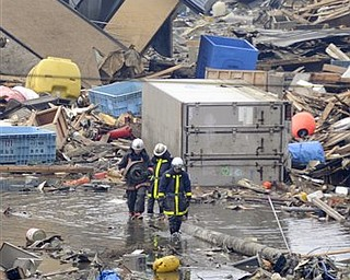 Firefighters shift through a devastated area in Kesennuma, northern Japan Tuesday, March 15, 2011 following Friday's massive earthquake and the ensuing tsunami.