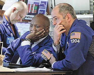 Specialists work at a post on the floor of the New York Stock Exchange Tuesday, March 15, 2011. Stocks have closed sharply lower Tuesday as the nuclear crisis in Japan weighed on global markets.