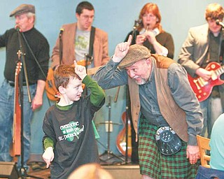 Kicking off St. Patrick's Day with the traditional unicorn song are William D. Lewis, right, and Michael Morgan, 6, of Liberty, the son of Jim and Kara Morgan. Lewis, a veteran Vindicator photographer, is part of County Mayo, an Irish band that played Wednesday for customers at Kravitz Deli in Liberty.